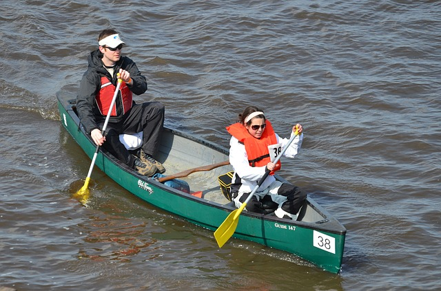 Kanot framförd av två kanotister med varsin enkelbladig paddel.